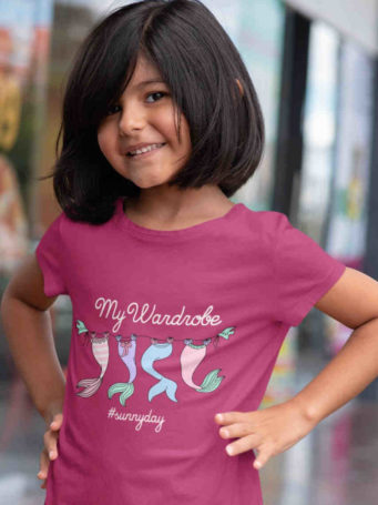 sweet girl in dark pink tshirt with Mermaid tails on clothesline